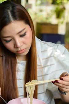 Jonge aziatenvrouw die noedelsoep eten