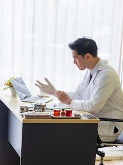 Jonge aziatische arts die witte rubberhandschoenen op een bureau draagt dat een computer heeft
