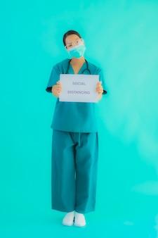 Jonge aziatische arts vrouw slijtage masker show sociale afstand op karton