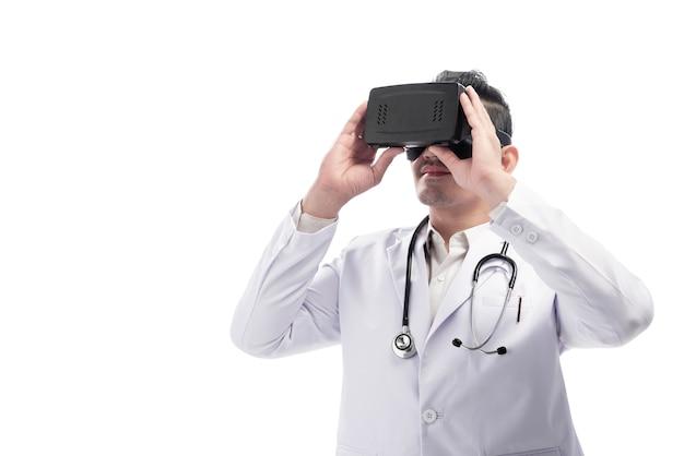 Jonge aziatische artsenmens met witte laboratoriumlaag en stethoscoop die virtuele werkelijkheid gebruiken