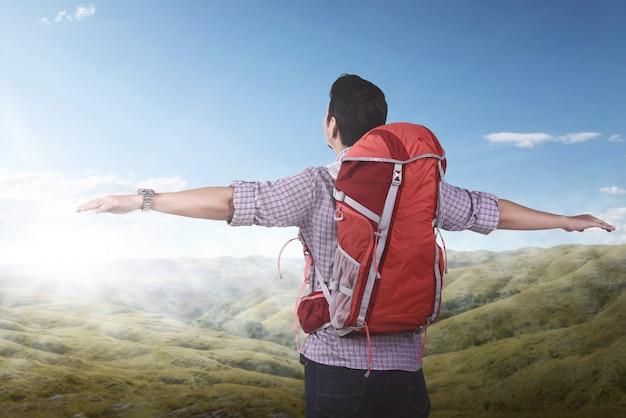 Jonge aziatische backpacker die van het landschap geniet