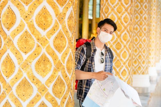 Jonge aziatische backpacker-man met gezichtsmasker die staat en de richting controleert op een papieren kaart in de hand bij een prachtige thaise tempel,