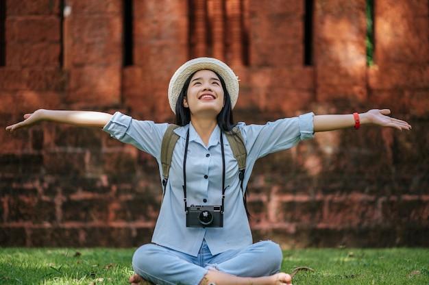 Jonge aziatische backpacker-vrouw met een hoed die lacht terwijl ze op een historische plek reist, ze zit op het gras om te ontspannen en gebruikt de camera om een foto te maken met gelukkig