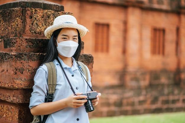 Jonge aziatische backpacker-vrouw met hoed en beschermingsmasker tijdens het reizen op een historische plek