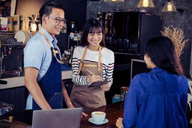 Jonge aziatische baristas die bij tegenbar in koffie opdracht geven tot