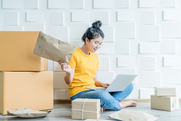 Jonge aziatische bedrijf opstarten online verkoper eigenaar met behulp van computer voor het controleren van de klant bestellingen van e-mail of website en het voorbereiden van pakketten