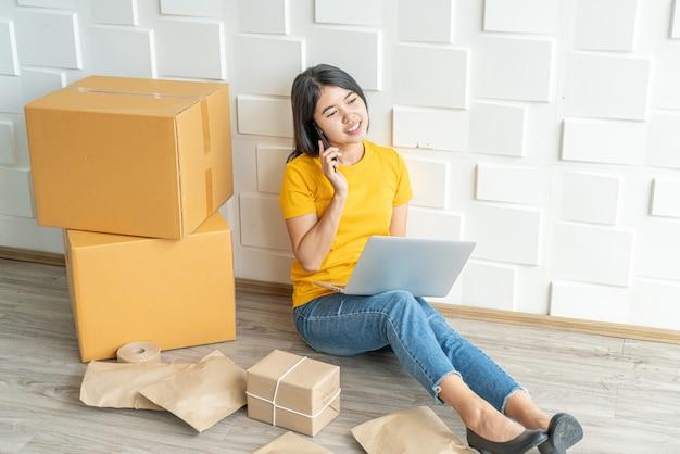 Jonge aziatische bedrijf start online verkoper-eigenaar met behulp van computer voor het controleren van de klantbestellingen van e-mail of website en het voorbereiden van pakketten