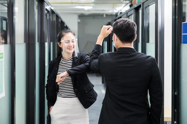 Jonge aziatische bedrijfscollega die gezichtsschild, gezichtsmasker en elleboogbuilgroet op gang in het bureau draagt