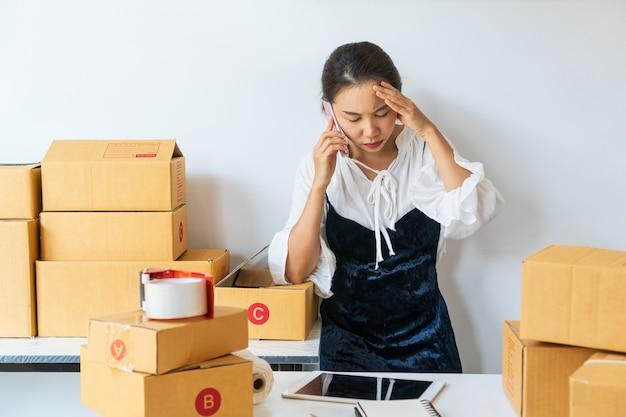 Jonge aziatische bedrijfseigenaar vrouw geïrriteerde klant en werken met saaie emotie. online verkopen, mkb-ondernemer of freelance werkconcept.