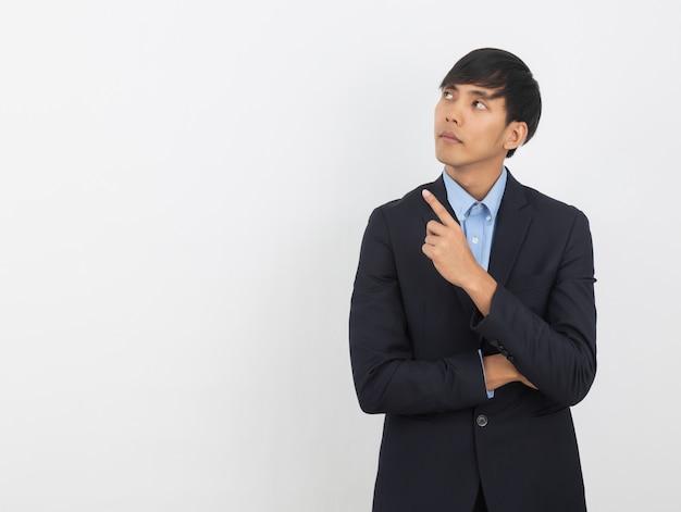 Jonge aziatische bedrijfsmens die aan de kant met een vinger richt om een product of een idee te presenteren terwijl vooruit geïsoleerd kijken