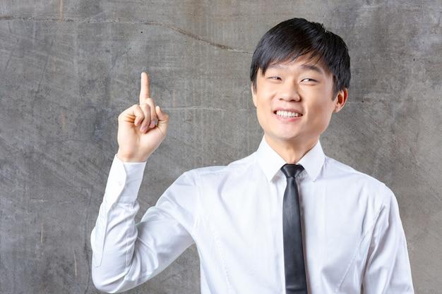 Jonge aziatische bedrijfsmens die iets toont