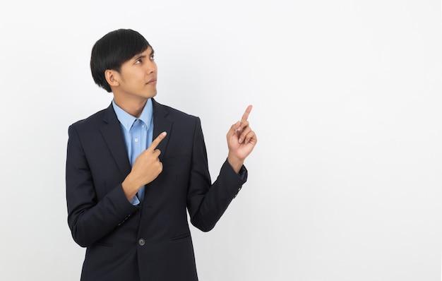 Jonge aziatische bedrijfsmens die met blauw overhemd aan de kant met een hand richt om een product of een idee te presenteren dat op wit wordt geïsoleerd
