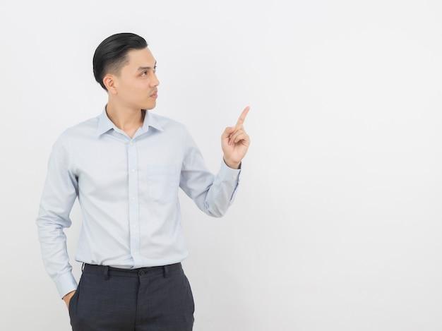 Jonge aziatische bedrijfsmens die met blauw overhemd aan de kant met een vinger richt om een product te presenteren