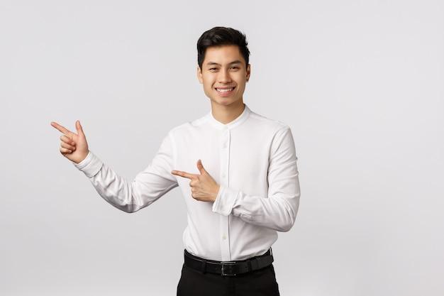 Jonge aziatische bedrijfsmens in een kostuum die met zijn vinger op richten.