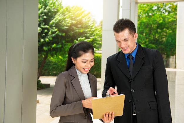 Jonge aziatische bedrijfsmensen die bedrijfsrapport bespreken