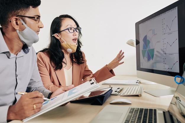 Jonge aziatische bedrijfsmensen die diagram op computerscherm bespreken en verkoopbronnen analyseren
