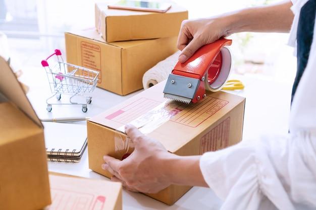 Jonge aziatische bedrijfsondernemer die een doos met band op het bureau verzegelt. voorbereiden voor verzending, verpakking, online verkopen, e-commerce concept. detailopname