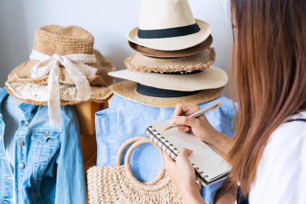 Jonge aziatische bedrijfsondernemer die voorraadsaldo controleert en nota neemt van notitieboekje.