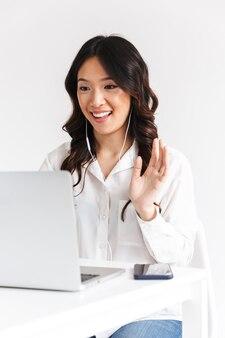Jonge aziatische bedrijfsvrouw bureaukleding dragen en oortelefoons die bij laptop, tijdens videogesprek golven