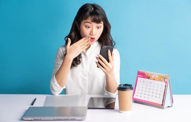 Jonge aziatische bedrijfsvrouw die aan blauw werkt