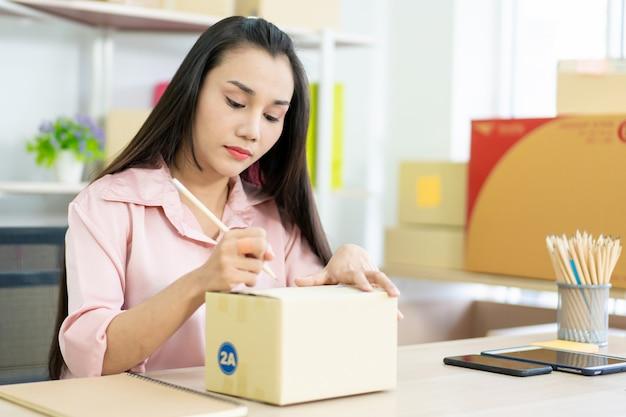 Jonge aziatische bedrijfsvrouw die brievenbussen inpakt die naar klanten moeten worden verzonden. e-commerce online shopping concept. expertise online verkoper die pakketdozen van klanten inpakt voor verzending.