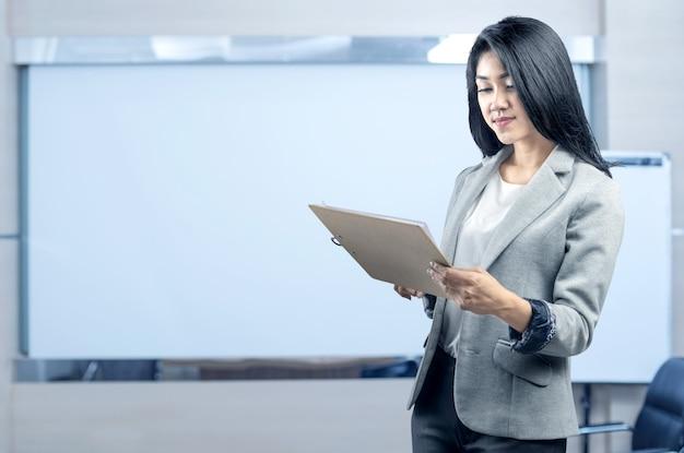 Jonge aziatische bedrijfsvrouw die en klembord bevindt zich houdt