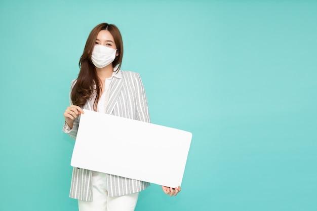 Jonge aziatische bedrijfsvrouw die gezichtsmasker draagt en holdings leeg wit aanplakbord toont dat op groene achtergrond wordt geïsoleerd