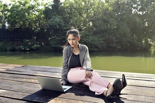 Jonge aziatische bedrijfsvrouw die met laptop werkt