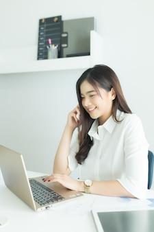 Jonge aziatische bedrijfsvrouw die op de mobiele telefoon en het glimlachen spreekt