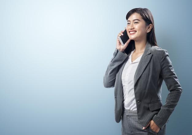 Jonge aziatische bedrijfsvrouw die op smartphone spreekt