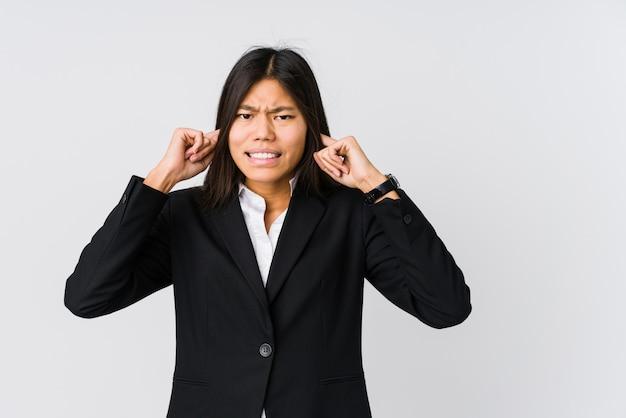 Jonge aziatische bedrijfsvrouw die oren behandelt met handen.