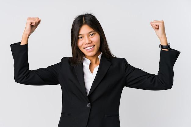 Jonge aziatische bedrijfsvrouw die sterktegebaar met wapens, symbool van vrouwelijke macht toont