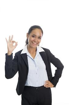 Jonge aziatische bedrijfsvrouw die terwijl het geven van ok teken glimlacht
