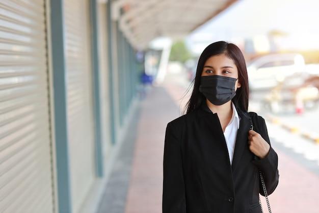 Jonge aziatische bedrijfsvrouw in zakelijk zwart kostuum met beschermmasker voor gezondheidszorg die op straat openbare openlucht lopen en weg kijken. nieuw normaal en sociaal afstandsconcept