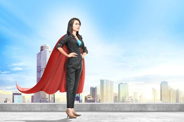 Jonge aziatische bedrijfsvrouw met rode kaap die zich op het dak bevindt