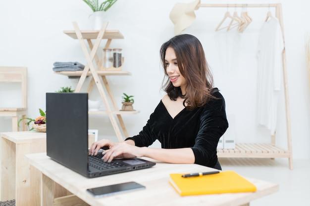 Jonge aziatische bedrijfsvrouwen die met computerlaptop bij haar winkel werken