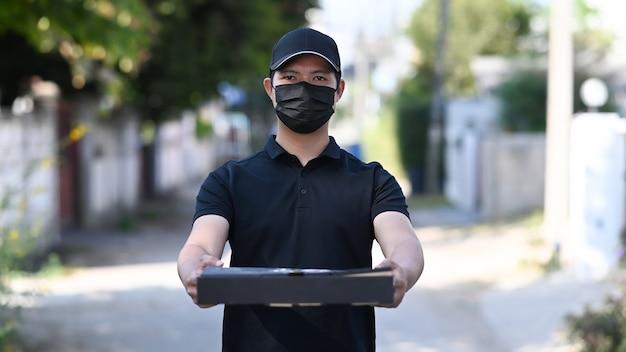 Jonge aziatische bezorger in beschermend masker met dozen met hete pizza.