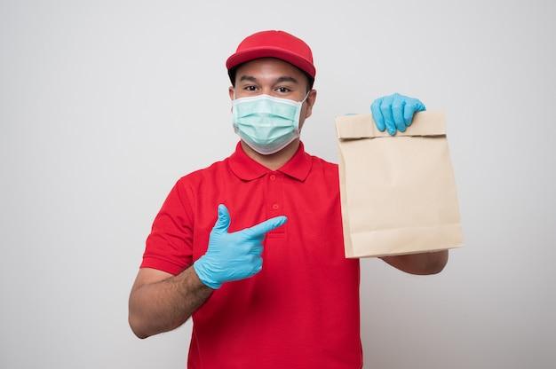 Jonge aziatische bezorger in uniform dragen van beschermend masker en rubberen handschoenen