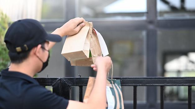 Jonge aziatische bezorger met beschermend masker die voedsel levert aan de klant bij de deuropening.