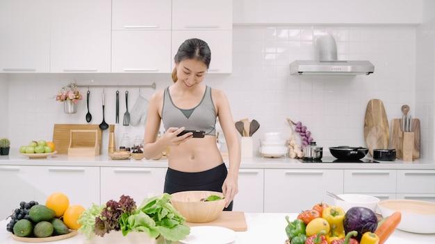Jonge aziatische bloggervrouw die smartphonefotopost gebruikt op sociale media in de keuken