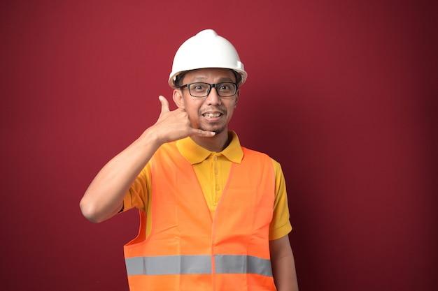 Jonge aziatische bouw man met helm gebaren bel me met zijn hand op rode achtergrond.