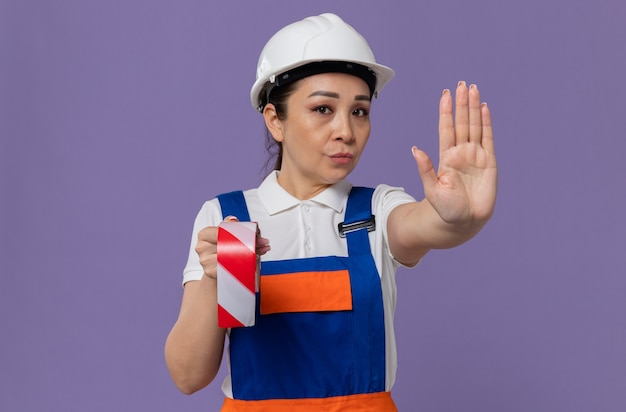 Jonge aziatische bouwvrouw met witte veiligheidshelm die waarschuwingsband vasthoudt en een stopbord gebaren