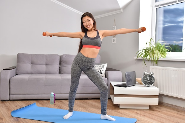 Jonge aziatische brunette vrouw in sportwear thuis training met twee oranje halters maken.