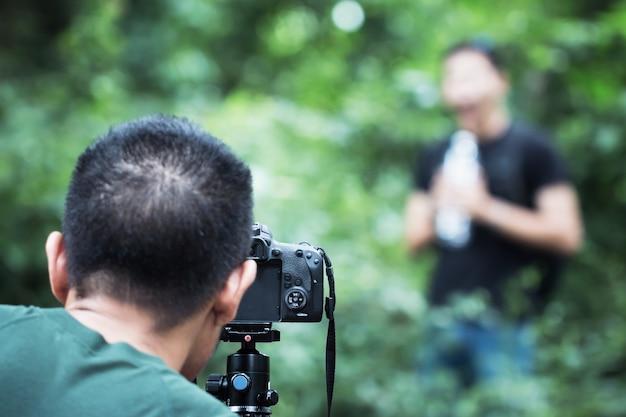 Jonge aziatische cameraman die videocamcorderinterviews of professionele digitale mirrorless plaatst