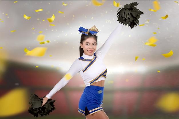 Jonge aziatische cheerleader met poms in haar handen