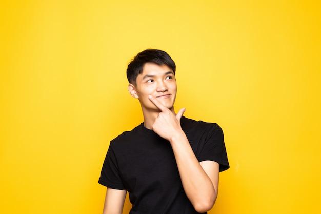Jonge aziatische chinese mens die met hand op kin over vraag denkt, peinzende uitdrukking die zich over geïsoleerde gele muur bevindt. glimlachend met een bedachtzaam gezicht. twijfel concept.