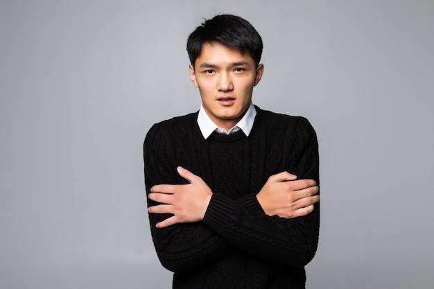 Jonge aziatische chinese mens wat betreft pijnlijke hals, keelpijn voor griep, kluit en infectie die zich over geïsoleerde witte muur bevinden