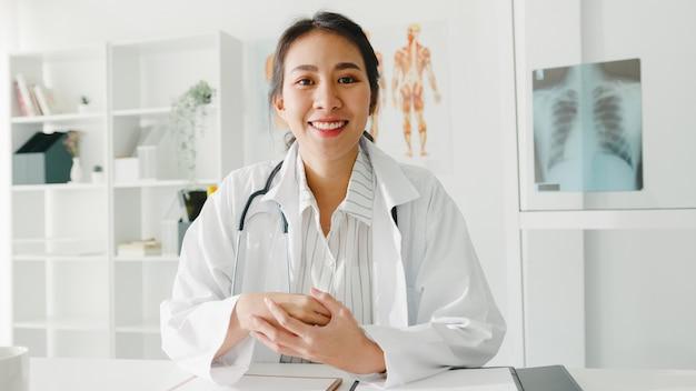 Jonge aziatische dame arts in wit medisch uniform met stethoscoop die computerlaptop met behulp van