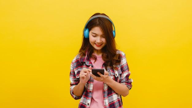 Jonge aziatische dame die draadloze hoofdtelefoons dragen die aan muziek van smartphone met vrolijke uitdrukking in vrijetijdskleding luisteren en camera over gele muur bekijken. gelaatsuitdrukking concept.