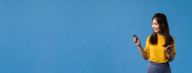 Jonge aziatische dame die telefoon en creditcard met positieve uitdrukking gebruikt, glimlach breed, gekleed in vrijetijdskleding en sta geïsoleerd op blauwe achtergrond. panoramische bannerachtergrond met exemplaarruimte.